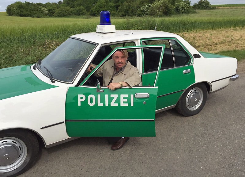 Schauspieler André Eisermann (im Polizei-Rekord aus Marburg) spielt im Taunuskrimi in einem Rückblick auf die 1980iger Jahre den Polizisten Konrad Ginsberg und zwar in einer Szene auf das Jahr 1982