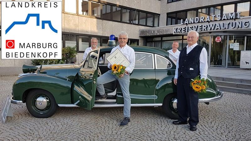 """Das Team vom Polizei-Motorsport-Club Marburg nach der Überreichung des Otto-Ubbelohde-Preises neben dem mitgebrachten Polizeioldie, dem BMW 501 - bekannt aus der Polizeiserie """"Isar 12"""""""