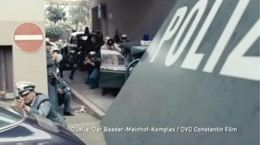 Ein Screenshot aus dem Film Baader Meinhof Komplex - in dieser Szene folgt ein Schusswechsel im Rahmen der Festnahme von Andreas Baader. Unser Opel Rekord und der VW Käfer sind dabei im Hintergrund zu sehen