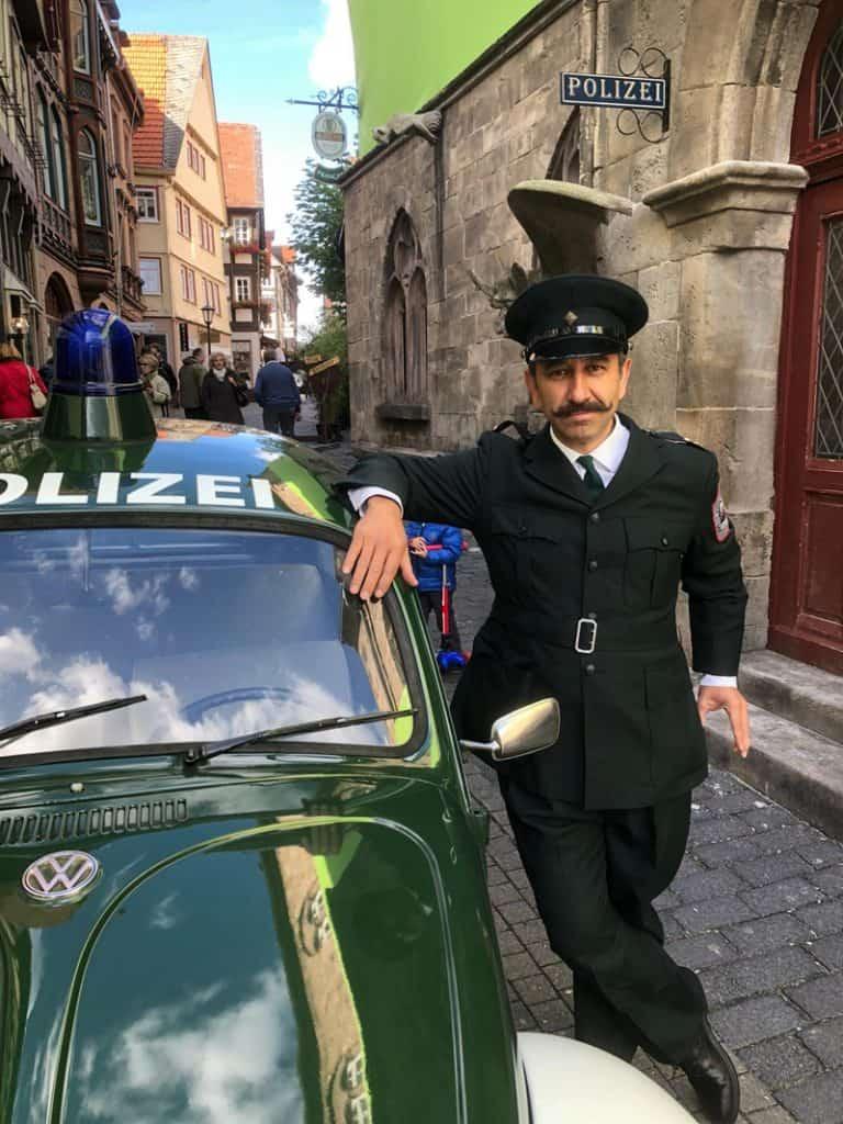 """Beim Dreh zu """"Die Wolf-Gäng"""" in der historischen Altstadt von Alsfeld steht Schauspieler Hilmi Sözer vor der dortigen Polizeiwache neben seinem Polizei-Einsatzfahrzeug, dem VW Käfer aus dem Polizeioldtimer Museum in Marburg."""