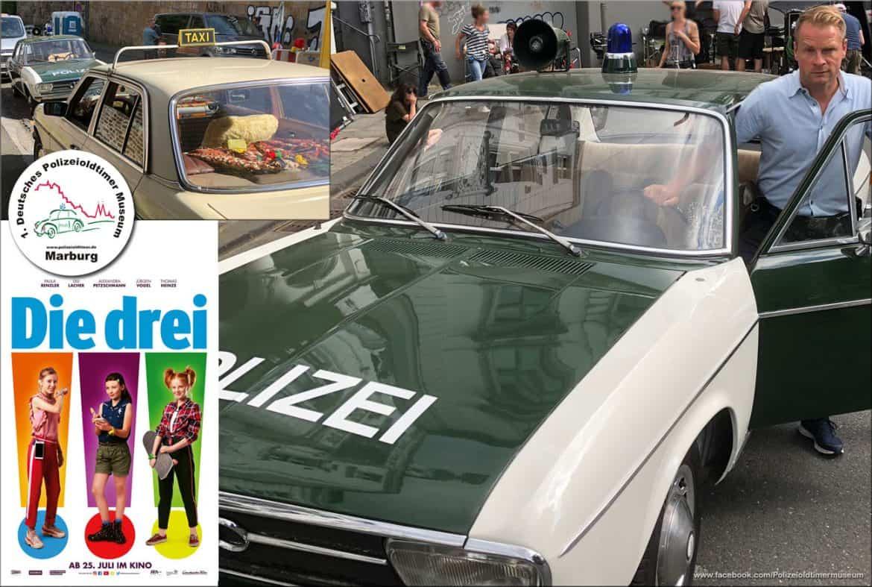 """Ein Bild mit Plakat zum Kinofilm """"Die drei Ausrufezeichen"""" mit dem Polizeioldtimer und Schauspieler Hinnerk Schönemann"""
