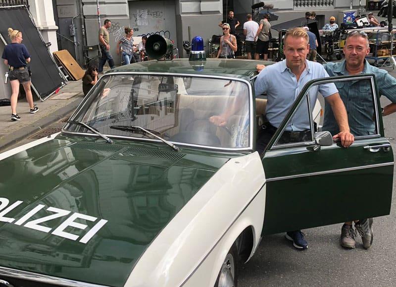 """Beim Dreh zu """"DIE DREI !!!"""" in Wuppertal, Schauspieler Hinnerk Schönemann mit Frank Dönges vom Polizeioldtimer Museum - neben dem Audi 100 aus Marburg"""
