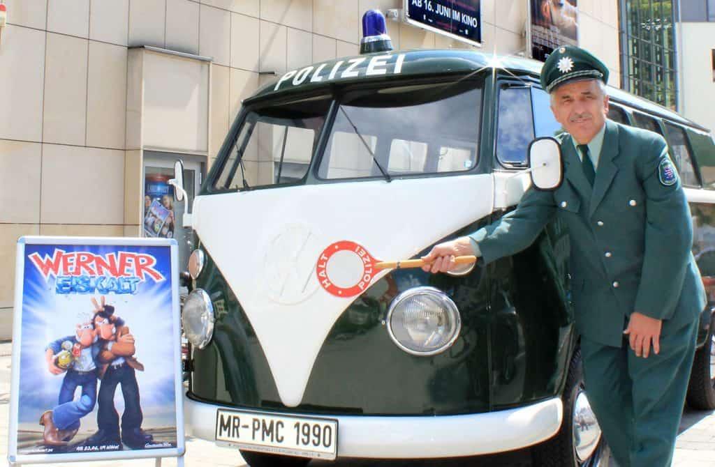 """Der Polizei-Bulli mit dem Plakat zum neuen Werner-Film """"Werner Eiskalt"""" vor dem Cineplex-Kino in Marburg mit Eberhard Dersch in historischer Polizeiuniform"""