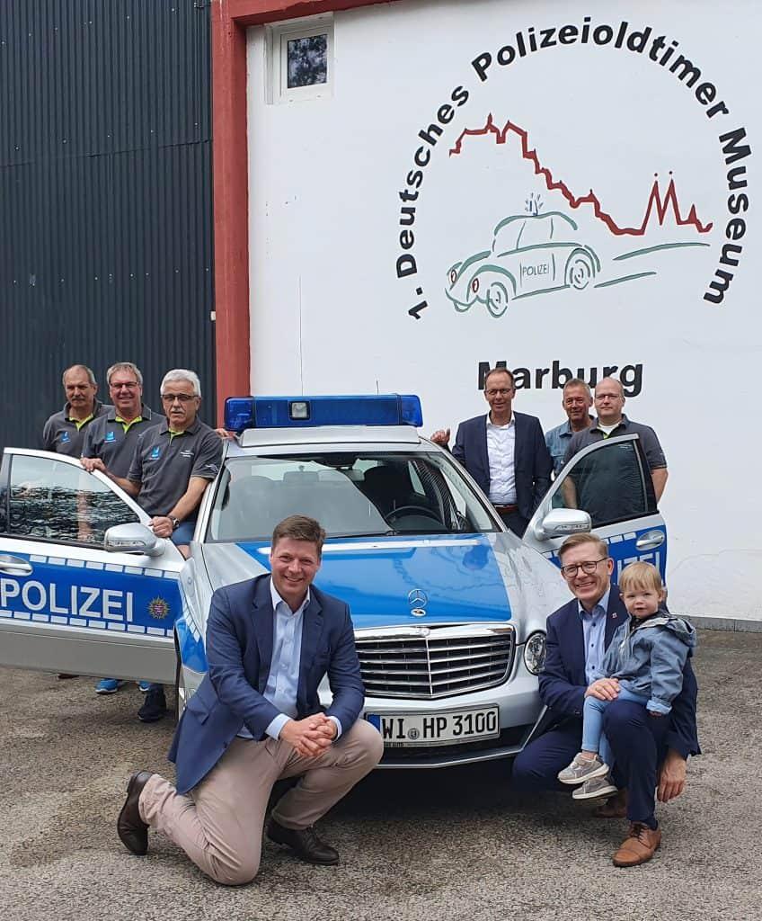 Fahrzeugübergabe des Mercedes Polizeifahrzeuges durch Staatssekretär Dr. Stefan Heck (vorne links) an den PMC Marburg, mit dabei das Vorstandsteam des PMC um den Vereinsvorsitzenden Eberhard Dersch (3 v.l.) sowie MdL Dirk Bamberger (vorne rechts) und der neue Leiter der Polizeidirektion Marburg, Kriminaldirektor Frank Göbel ( hinten 3. von rechts)